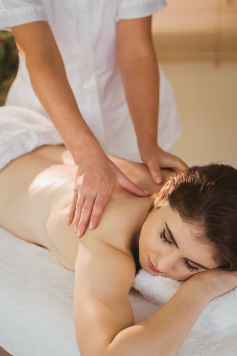 Young woman getting back massage in therapy room